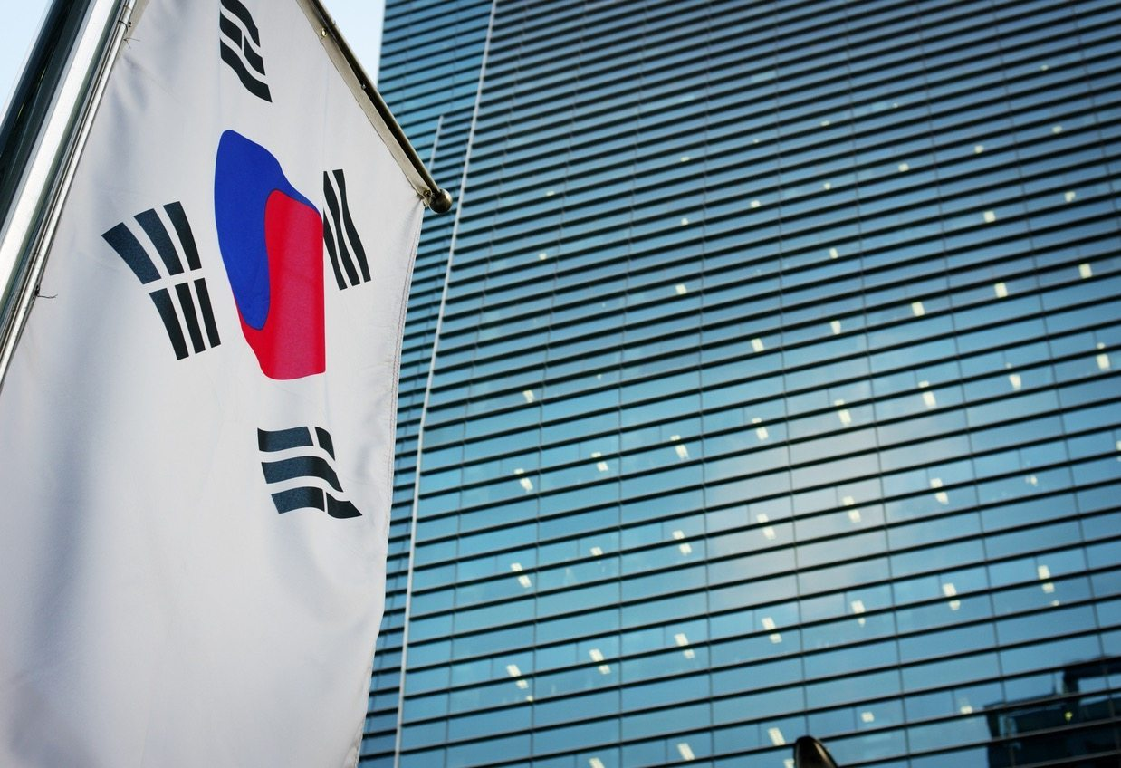 Feature Image: Korean flag in the foreground, an office building in the background. Picture is taken in Seoul, South Korea.