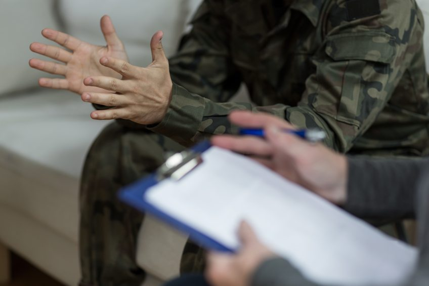 Soldier sitting on the sofa next to person with clipboard